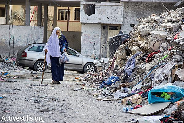Palestinian woman walks between the ruins of Beit Hanoun, North Gaza Strip, August 12, 2014.  (Basel Yazouri/Activestills.org)