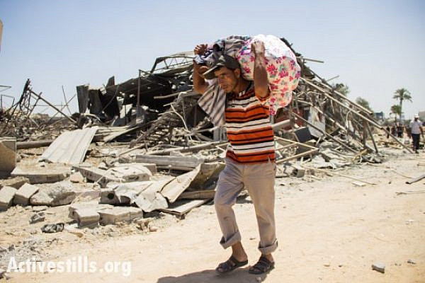 Palestinians recover belongings from the Khuza'a neighborhood following bombardment by Israeli forces, Gaza Strip, August 1, 2014.