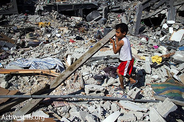 Nader Obu Odeh, 6 years old, gathers some wood from destroyed houses to help make a fire. August 12, 2014. (Basel Yazouri/Activestills.org)