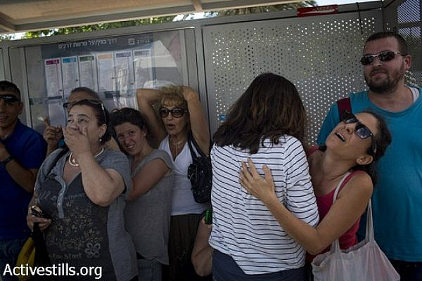 Israelis take cover near a bus stop in a street in center Tel Aviv during a siren alarm as a rocket Is launched from Gaza strip, August 3, 2014. (Oren Ziv/Activestills.org)