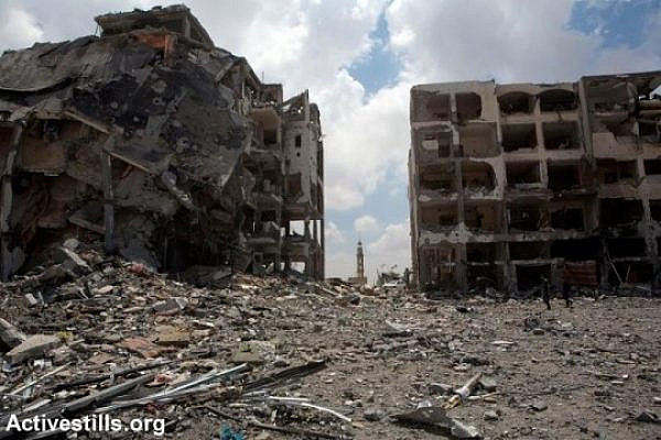 A mosque minaret rises among the ruins of Al-Nada towers after they were destroyed by Israeli strikes in Beit Hanoun, northern Gaza Strip, August 4, 2014. The towers had 90 flats. So far, Israeli attacks have killed at least 1,870 Palestinians, and injured 9,470 since the beginning of the Israeli offensive (photo: Activestills)