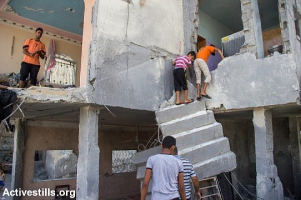 Palestinians retrieve belongings from their destroyed home in Beit Hanoun, northern Gaza Strip, August 12, 2014. According to OCHA, 16,800 homes in the Gaza Strip have been destroyed or severely damaged, leaving 370,000 displaced. (photo: Activestills)