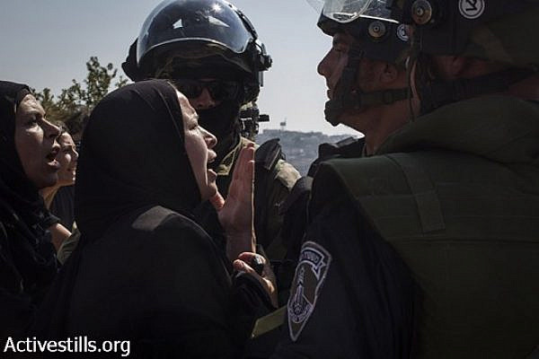 Palestinian women argue with an Israeli soldiers, after a Palestinian youth was shot with live ammunition and was taken by the army, during the weekly protest against the occupation, in the West Bank village of Nabi Saleh, August 15, 2014. (Keren Manor/Activestills.org)