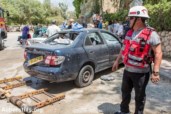 Israelis check the scene in which a rocket shot from the Gaza Strip has hit a street in the city of Beer Sheva, August 22, 2014. (photo: Activestills)