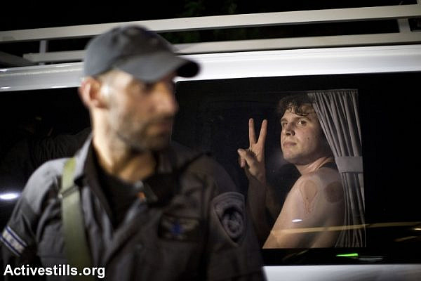 A leftist demonstrator looks on after being arrested by police during an anti-war demonstration in Tel Aviv. (photo: Keren Manor/Activestills.org)