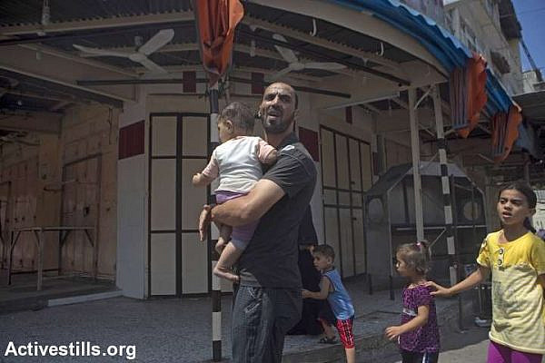 Palestinians from Shejaiya area flee their homes and look for shelter in Gaza city following a large-scale Israeli attack on their neighborhood, Gaza City, July 20, 2014. Spokesman of the Palestinian ministry of health Ashraf al-Qidra said rescue teams evacuated more than 80 dead bodies from destroyed houses in Shejaiya including 17 children, 14 women and 4 elderly people. More than 200 injured people were taken to al-Shifa Hospital. Death toll in the Gaza Strip accedes 392 with over 2650 wounded since the beginning of the Israeli offensive. (photo: Anne Paq / activestills)