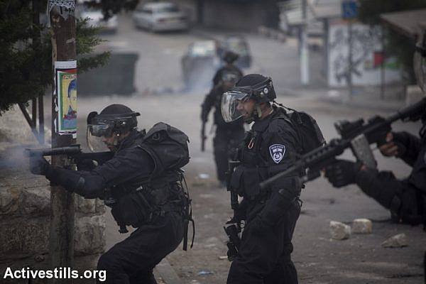An Israeli policeman shoots tear gas during a protest following the death of a Muhammad Sunuqrut, in the neighborhood of Wadi Joz in East Jerusalem on September 8, 2014. Muhammad Sunuqrut, 16, was wounded by police gunfire in the Wadi Joz neighborhood on August 31 and died from his injuries on September 7. (photo: Activestills)