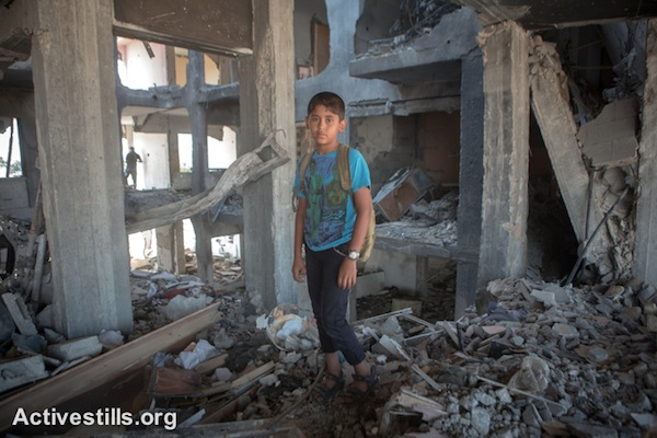 Mohammed, age 11, stands in the remains of his home in the Al Nada Towers of Beit Hanoun in the northern Gaza Strip after they were destroyed by Israeli strikes. The towers had 90 apartments, home to many families. (photo: Activestills.org)