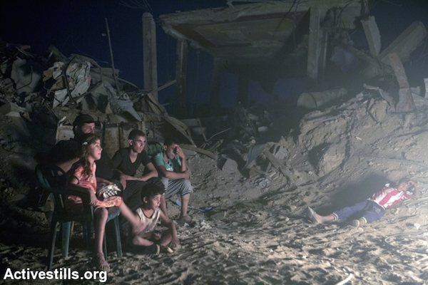 Palestinians gather around a fire in the at-Tuffah district of Gaza city, which was heavily attacked during Israel's latest offensive, Gaza City, September 6, 2014. The family of eight returned to their home, which is in danger of collapse due to the damage. Their home, like all the buildings in the area, is neither connected to the electricity or water infrastructure. (Photo by Anne Paq/Activestills.org)