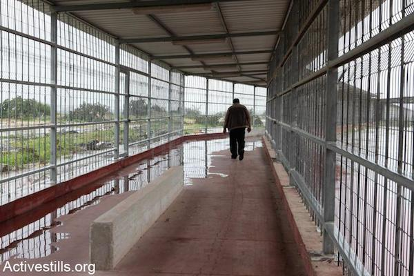 A Palestinian man from Gaza walks down an open air corridor at the Erez Crossing terminal, the northern checkpoint leading from the Gaza Strip to Israel, in the area of Beit Hanun, February 14, 2012. (Photo by Anne Paq/Activestills.org)