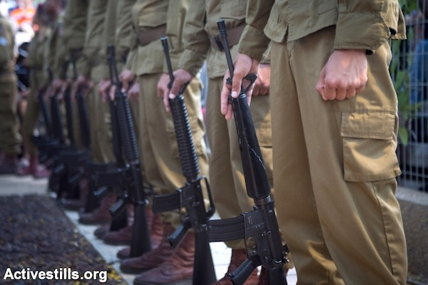 Soldiers in an IDF honor guard hold their weapons during the funeral for a soldier killed in Gaza, July 20, 2014, Holon, Israel. (Photo by Oren Ziv/Activestills.org)