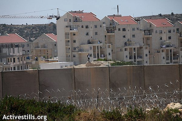 "Israel's separation barrier stands on land belonging to the Palestinian village of Bil'in; the wall was built surrounding the Israeli settlement of Modi'in Illit (seen in the background). In a protracted court battle, Bil'in managed to win back some of its land but landowners are still cut off from a significant portion which has been appropriated by the Jewish settlement - both to build on and as a ""security zone."" (Anne Paq/Activestills.org)"