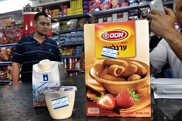 Stickers mark Israeli goods at a grocery store in Ramallah. (Photo by Jessica Devaney/Just Vision)