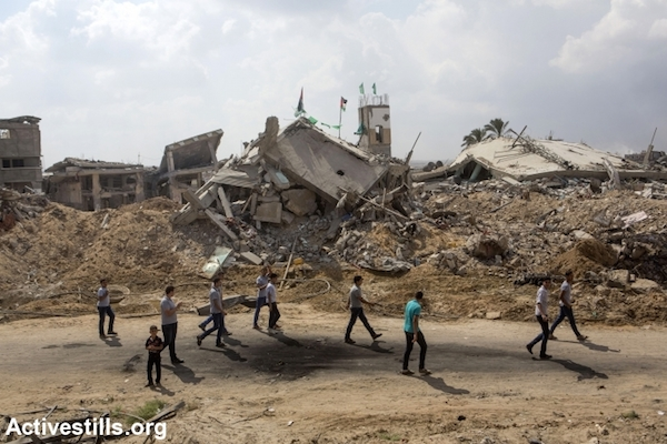 Palestinian school students pass by some destroyed buildings and homes in the Shujaiya neighborhood, Gaza city, September 15, 2014. (Photo by Anne Paq/Activestills.org)