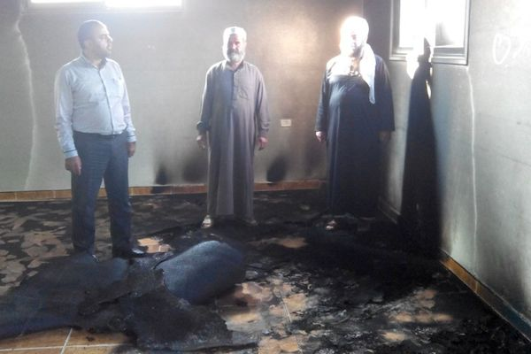 Palestinians survey the damage inside Aqraba's mosque, which was set on fire early Tuesday morning, October 14, 2014. (Photo by Rabbis for Human Rights)