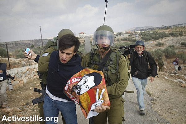 Israeli soldiers arrest an Israeli protester during a demonstration against the separation wall in the West Bank village of Bil'in. (photo: Oren Ziv/Activestills.org)