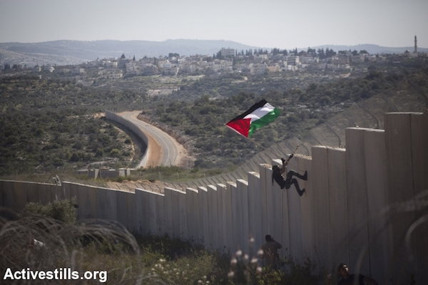 A Palestinian youth places a flag on the Israeli wall during a protest marking nine years of struggle against the wall in the West Bank village of Bilin, February 28, 2014. (Photo by Oren Ziv/Activestills.org)