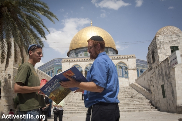 Right-wing activist Yehuda Glick holding a book depicting the Jewish Temple while standing in front of the Aqsa Mosque in Jerusalem, May 21, 2009. (Photo by Oren Ziv/Activestills.org)