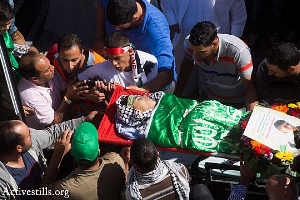 Mourners carry the body of 14-year-old Palestinian-American Orwah Hammad at his funeral in the West Bank village of Silwad, October 26, 2014. (Photo by Oren Ziv/Activestills.org)