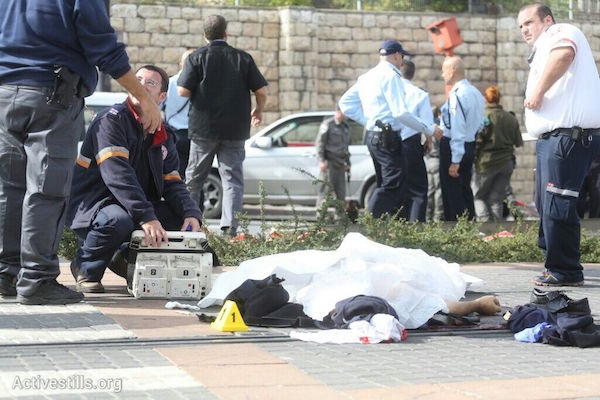 Police investigators stand around the body of a Palestinian man who ran over a group of Israeli pedestrians in Jerusalem, November 5, 2014. Police shot and killed the man shortly after the attack. (Photo by Oren Ziv/Activestills.org)