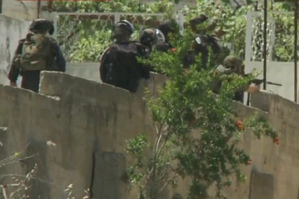 Screenshot of CNN footage showing what appears to be a Border Police officer shooting at demonstrators in Beitunia on Nakba Day, May 15, 2014. In the video, a puff of smoke and shell can be seen coming from the third-to-left officer's weapon.