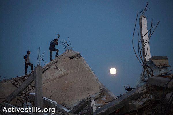 Palestinians salvage materials from destroyed homes at night in the village of Khuza'a, eastern Gaza Strip, November 6, 2014. (Anne Paq/Activestills.org)