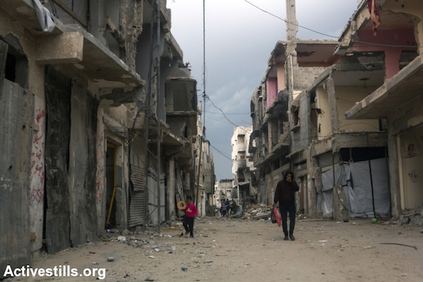 Palestinians walk through the Shujayea neighborhood of Gaza City, nearly three months since a cease fire ended Operation Protective Edge, November 16, 2014. (Photo by Anne Paq/Activestills.org)