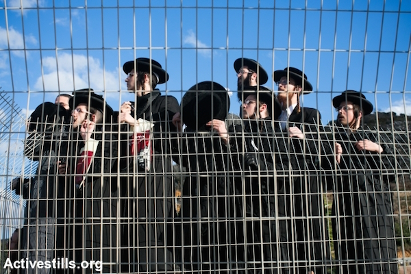 Ultra-Orthodox Jews gather during a protest against their military conscription outside a military prison on December 9, 2013 in Atlit, Israel. Hundreds of Ultra-Orthodox Jews protested outside the prison following the arrest of a young man who refused to serve in the Israeli the army, September 12, 2013. (Photo by Yotam Ronen/Activestills.org)