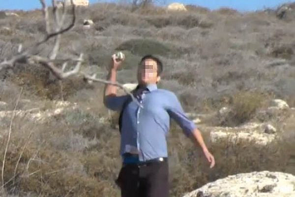 Settler from Pnei Kedem throws stones at Palestinian farmers. (YouTube screenshot)