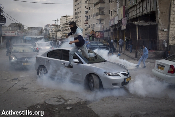 A Palestinian runs to take cover from tear gas during clashes with Israeli police in the Palestinian refugee camp of Shuafat in east Jerusalem, on November 5, 2014
