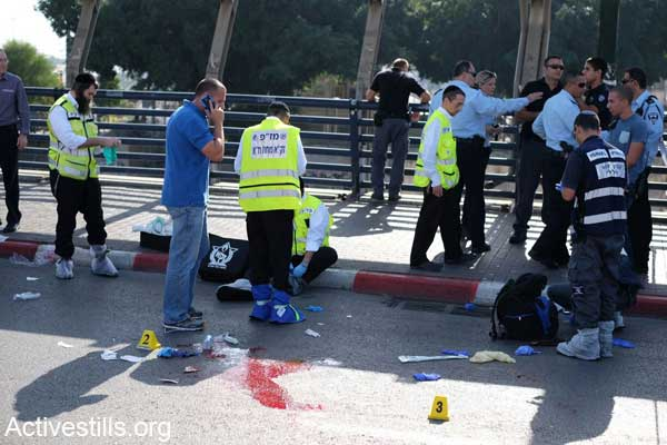 Police investigators collect evidence and ZAKA volunteers collect blood from the spot where an Israeli soldier was stabbed and killed Monday outside a Tel Aviv train station, November 10, 2014. (Photo by Yotam Ronen/Activestills.org)