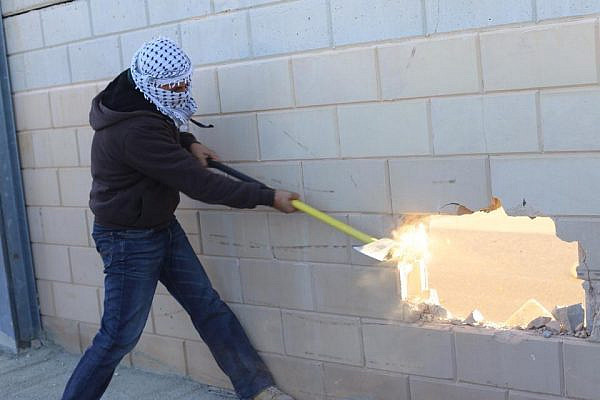 A Palestinian smashes a hole through the separation wall near Jerusalem. (photo: Popular Struggle Coordination Committee)
