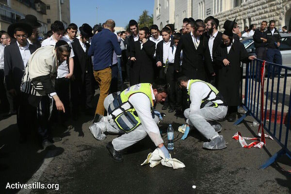 ZAKA volunteers collect blood, according to Jewish ritual, at the scene of a Jerusalem synagogue where two Palestinians killed four worshippers and seriously wounded eight others, November 18, 2014. (Photo by Oren Ziv/Activestills.org)