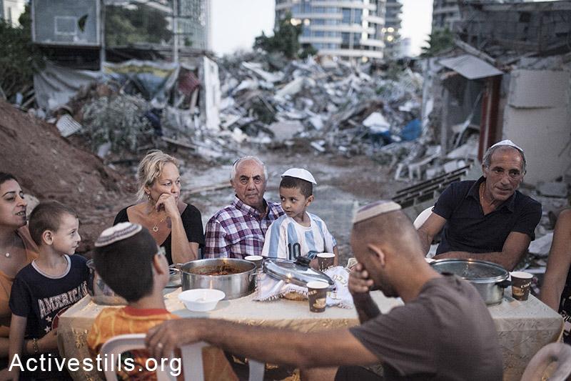 The Kadoori, Hamias, and Ashram families sit at an improvised Shabbat dinner table next to their demolished houses in Givat Amal, Tel Aviv, Sep. 19, 2014. (Shiraz Grinbaum/Activestills.org)