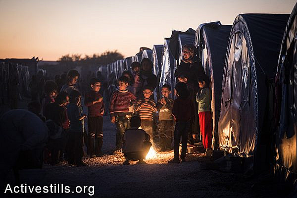 Refugee warm up near a fire at the Arin Mirkhan refugee camp, Turkish-Syrian border, October 2014. Photo: Faiz Abu-Rmeleh/Activestills.org