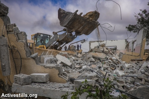 A Bedouin family demolishes its own home in the unrecognized village of Sawa, Negev Desert, December 23, 2014. (photo: Yotam Ronen/Activestills.org)