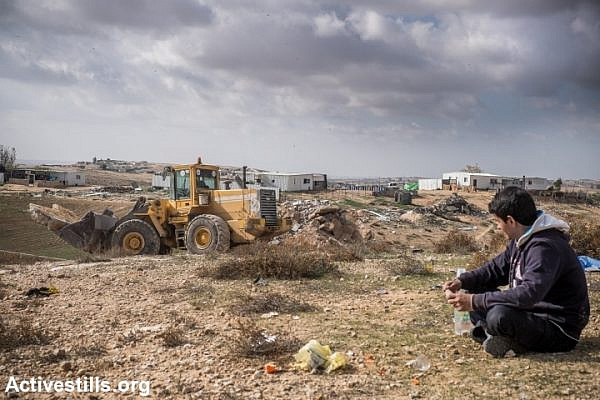 A young Bedouin watches as a bullzdozer rented by his family demolishes their own home in the recognized village Sawa, Negev Desert, December 23, 2014. (photo: Yotam Ronen/Activestills.org)