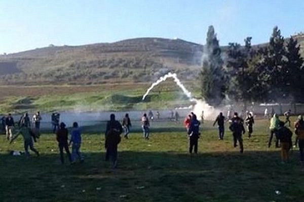 Tear gas being fired into the yard of a high school in the Palestinian village of Burin, December 15, 2014. (Photo by Zakaria Sadah/Rabbis for Human Rights)