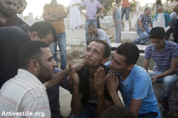 A relative of a child killed earlier in a playground in al-Shati refugee camp mourns at a cemetery, Gaza City, July 28, 2014. Reports indicated that 10 people, mostly children, were killed and 40 injured during the attack which took place on the first day of the Muslim holiday of Eid. (Photo by Anne Paq/Activestills.org)