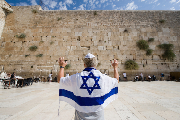 Illustrative photo of a man wearing an Israeli flag at the Western Wall. (By Shutterstock.com / Robert Hoetink)