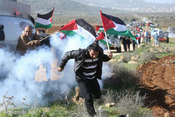 Palestinian protesters flee tear gas at a non-violent protest in which Palestinian Minster Ziad Abu Eid died. Activists set out to plant olive trees on lands usurped by Israeli settlements, December 10, 2014. (Photo by Oren Ziv/Activestills.org)
