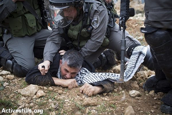Israeli border policemen arrest Palestinian activist Muhammad Khatib during a demonstration commemorating the death of Palestinian minister, Ziad Abu Ein, in the West Bank village of Turmus Aya, north of Ramallah, December 19, 2014. (photo: Oren Ziv/Activestills.org)