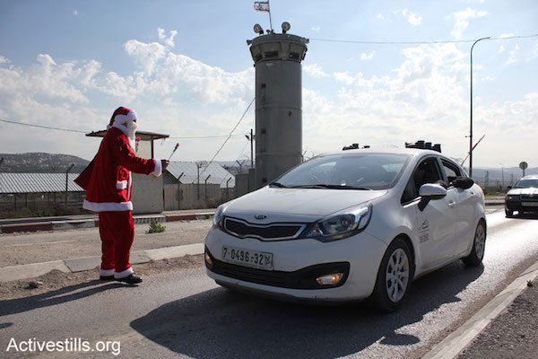 A Palestinian man dressed as Santa Claus hands out flowers cars passing through the Huwwara military checkpoint, south of Nablus, during a protest against Israeli occupation, January 1, 2015. One protester was arrested during the action. (Photo by Ahmad Al-Bazz/Activestills.org)