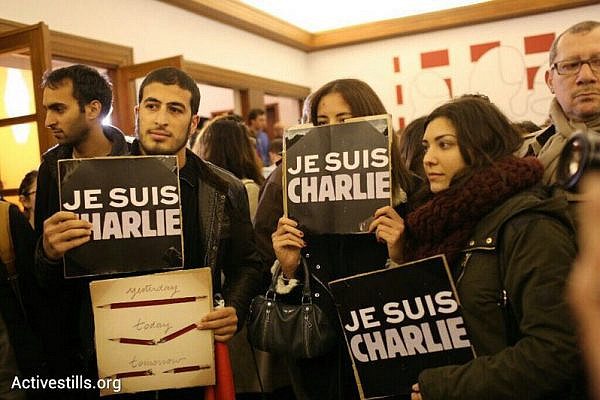 "French nationals hold up signs reading ""I am Charlie"" during a vigil at the French Embassy in Tel Aviv, January 8, 2015. (photo: Oren Ziv/Activestills.org)"