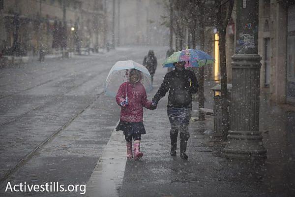 A couple walks during a snowstorm in Jerusalem, January 7, 2015. (photo: Oren Ziv/Activestills.org)
