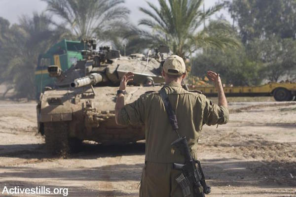 File photo of an Israeli soldier directing a tank. (Photo by Oren Ziv/Activestills.org)