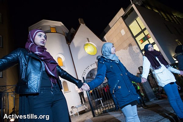 "Young Muslim women stand hand-in-hand in front of the Oslo Synagogue during the ""Ring of Peace"" vigil, February 21, 2015. The vigil was organized by Muslim youth in solidarity with Norway's Jewish community following anti-Jewish attacks in Denmark and other parts of Europe."