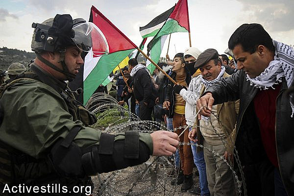 Palestinians from the West Bank village of Azzun protesting near Israeli soldiers for the opening of the eastern gate to the village, which has been closed by Israel since 1990, February 14, 2015. Ahmad al-Bazz / Activestills.org
