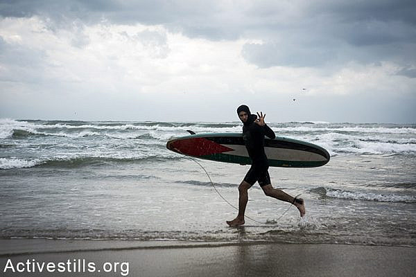 A youth runs to the water with his surfboard, Gaza beach, February 12, 2015. Anne Paq / Activestills.org
