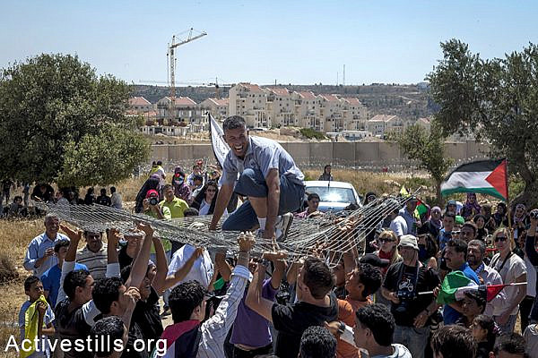 Mohammed Khatib, a Palestinian activist, is carried by the crowd celebrating in front of the Modiin Illit settlement following last week's moving of a section of the Separation Wall from lands belonging to the West Bank village of Bil'in, near Ramallah, July 1st, 2011. The village has started holding regular protests against the building of the Separation Wall on its lands and the occupation since 2005. Anne Paq / Activestills.org